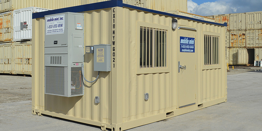 Equipped mobile office trailer shown among stacks of storage containers